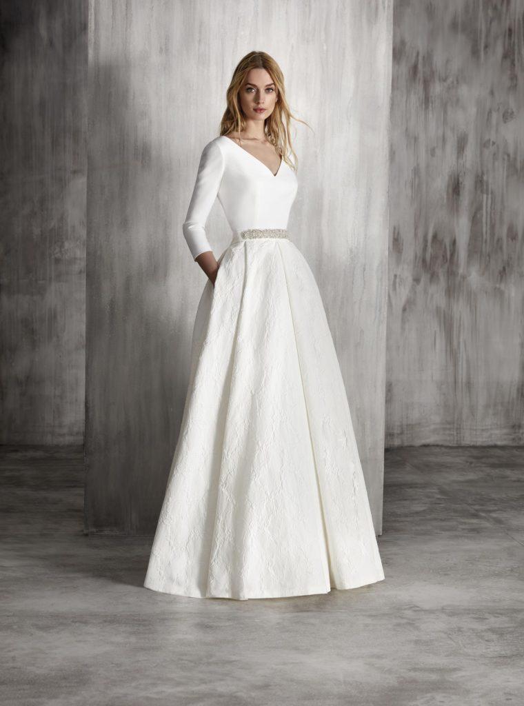 a7b83b310f El primer diseño es un vestido romántico con falda con volumen tableada en  brocado. La cintura está adornada con una aplicación de cristal.